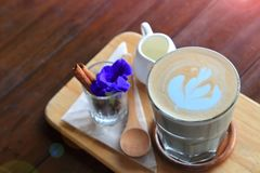 Coffee latte art served in classic Italian glass on wooden board with cinnamon stick and blue pea flower and additional syrup on r. Ustic table in the local cafe stock image