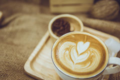 Coffee latte art served on wood plate decorated in cafe royalty free stock images