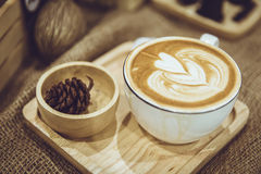 Coffee latte art served on wood plate decorated in cafe stock image