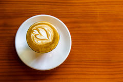 Coffee latte art in small glass on wooden background, Top view Stock Images