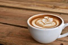Coffee latte art in white coffee cup. On wooden table background and copy space stock photos