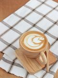 Coffee Latte Art in wood cup on tray and garment,with spoon. Top view stock photo
