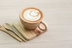 Coffee Latte Art in wood cup on tray and ,with spoon and fork. Closed up Coffee Latte Art in wood cup on tray and ,with spoon and fork royalty free stock photo