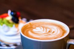 Coffee latte art on wood table and blurred piece of cake with fruits on the background.  stock image
