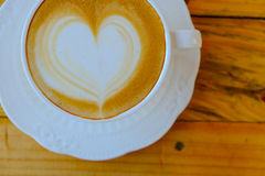 Coffee latte art on wood table cup Stock Photos