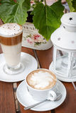 Coffee latte and cappuccino cafeteria garden table Royalty Free Stock Image