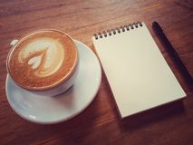 Coffee latte or cappuccino coffee with notebook Royalty Free Stock Photo