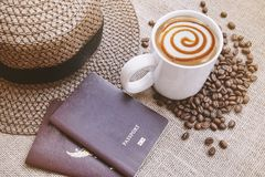 Coffee latte caramel macchiato with passport and weave hat, Traveling concept with copy space or text space. Conceptual of travel: Dark brown weave hat with Stock Image