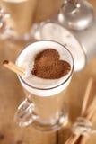 Coffee latte with cinnamon sticks and alarm Royalty Free Stock Image