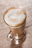 Coffee latte with closeup froth on rustic Royalty Free Stock Photo