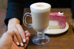Coffee latte with foam and cake female hand in male Stock Images