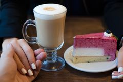 Coffee latte with foam and cake female hand in male Royalty Free Stock Images