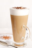 Coffee latte with frothy milk in tall glass royalty free stock photography