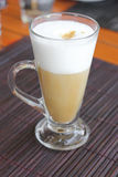 Coffee latte with frothy milk in tall glass. Royalty Free Stock Image