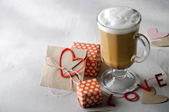 Coffee Latte with gift boxes, envelope and paper hearts. Pink, red, white colors on bright background. Love, Valentine`s Royalty Free Stock Photos
