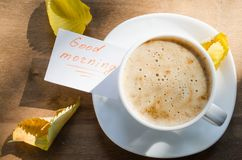 Coffee latte and the Inscription Good Morning. Cappuccino or coffee latte with foam in white cup and the Inscription Good Morning on wooden table. Autumn Stock Photography