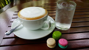 Coffee latte and macarons. Spicy colorful cooking food ice water  morning Royalty Free Stock Image