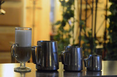 Coffee latte and milk pitchers Royalty Free Stock Photos