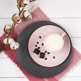Coffee latte on the pink and gray pastel plate with chocolate and branch cotton wood background coral napkin top view. Coffee latte on the pink and gray pastel royalty free stock image