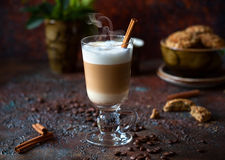 Coffee latte. In a tall glass with stick of cinnamon royalty free stock photography