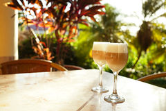 Coffee latte in tall glasses with morning sun in summer cafe bac Royalty Free Stock Photos