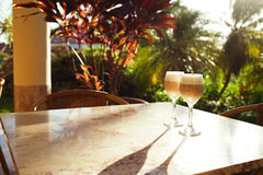 Coffee latte in tall glasses with morning sun in summer cafe bac Royalty Free Stock Photography