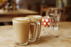 Coffee latte in two tall glasses and sugar bowl Royalty Free Stock Images