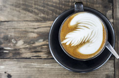 Coffee latte on wood table. A cup of coffee latte on old wood table Royalty Free Stock Photography