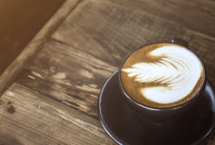 Coffee latte on wood table. A cup of coffee latte on old wood table Stock Photos