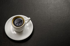Coffee and leather. Rich, black coffee in a white cup, lit beautifully and placed on a black leather texture Stock Photography
