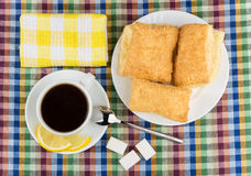 Coffee, lemon and sugar, plate with flaky biscuits on tablecloth Royalty Free Stock Image