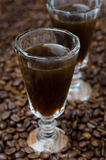 Coffee liqueur into a shot glass, selective focus close-up Royalty Free Stock Images