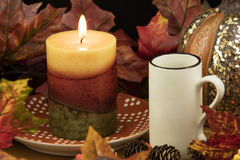 Coffee, Lit Candle and Pumpkin Decor Stock Image