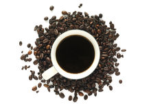 Coffee with loose beans. A cup of coffee siting on a pile of loose coffee beans Stock Photography