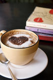 Coffee with love. Cup of cappuccino coffee on saucer, chocolate heart on top Stock Photography