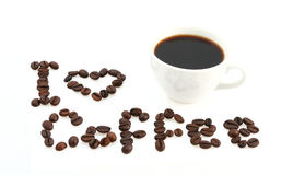 Coffee love. White coffee cup and text written with coffee beans Stock Images