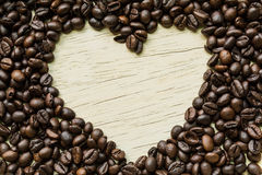 Coffee love, Coffee beans make a heart shape on a piece of wood. Coffee beans decorated heart-shaped piece of wood as a background Royalty Free Stock Images