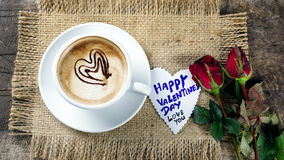 Coffee love with hearts on milk, Latte coffee. A cup of latte, cappuccino or espresso coffee with milk put on a wood table with dark roasted coffee beans Royalty Free Stock Photo