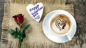 Coffee love with hearts on milk, Latte coffee. A cup of latte, cappuccino or espresso coffee with milk put on a wood table with dark roasted coffee beans Stock Photo