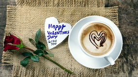 Coffee love with hearts on milk, Latte coffee. A cup of latte, cappuccino or espresso coffee with milk put on a wood table with dark roasted coffee beans Royalty Free Stock Image