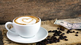 Coffee love with hearts on milk, Latte coffee. A cup of latte, cappuccino or espresso coffee with milk put on a wood table with dark roasted coffee beans Stock Images