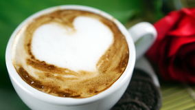 Coffee love with hearts on milk, Latte coffee. A cup of latte, cappuccino or espresso coffee with milk put on a wood table with dark roasted coffee beans Royalty Free Stock Photography