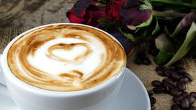 Coffee love with hearts on milk, Latte coffee. A cup of latte, cappuccino or espresso coffee with milk put on a wood table with dark roasted coffee beans Royalty Free Stock Photos