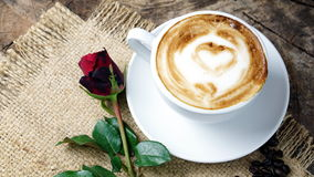 Coffee love with hearts on milk, Latte coffee. A cup of latte, cappuccino or espresso coffee with milk put on a wood table with dark roasted coffee beans Royalty Free Stock Images