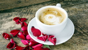 Coffee love with roses on milk, Latte coffee art. A cup of latte, cappuccino or espresso coffee with milk put on the wood table  with dark roasted coffee beans Royalty Free Stock Image