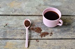 Coffee lover. Pink cup of coffee and tea spoon with on a wooden table Stock Photo