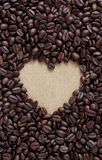 Coffee lover sign, Pile of brown coffee beans in heart shape. Close up of coffee beans in love symbol on sack cloth royalty free stock photography