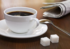 Coffee, lump sugar and newspaper on a table Royalty Free Stock Photo