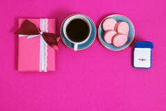 Coffee with macarons and ring on a pink background. An offer of marriage, box which give ring. Top view, toned image. Coffee with macarons and ring on a pink Stock Images