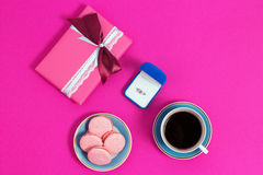 Coffee with macarons and ring on a pink background. An offer of marriage, box which give ring. Top view, toned image. Coffee with macarons and ring on a pink Royalty Free Stock Images